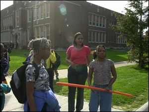 Leigh Miller (center) arrives to take her daughter, student crossing guard Kenia Quinn, home from Warren Elementary School. A parent whose child has attended Warren since it reopened in near-downtown Toledo in 1995, Ms. Miller says the school's curriculum should reflect the skills tested on Ohio proficiency tests, but it doesn't.