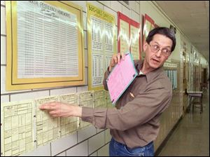 Dennis Lynn points out his popular assignments-on-the-wall practice. The hallway walls at Newton D. Baker Elementary School are like his canvas for learning materials. Mr. Lynn, a Title 1 teacher at the school, is called 'the best math teacher in the whole state of Ohio' by his former principal.