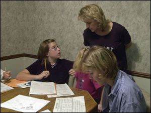 Lynette Westphal, standing, says the amount of homework that daughters Allison Lawrence, 11, left and Amanda Westphal, 16,