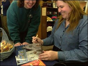 Laura Lee, right, signs a copy of her book, pictured at right, for Jennifer Hunt of Swanton at Thackeray's Books.