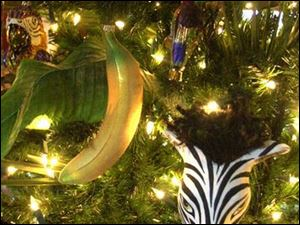 The den features a tree decorated with a safari theme, including zebra and animal-print ornaments.