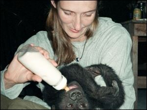Belinga watches what's going on behind her as Linda Percy tries to give her a bottle before bed.