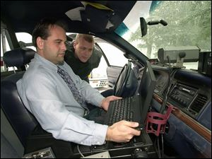 Councilman Mike Edenius uses one of the new laptop computers as police Chief David Graham looks on.