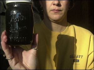 Vickie Wilkins of Lambertville, Mich., displays dirty water she removed from one of her filters. She said she is eight signatures short of the number needed to ask for city water.