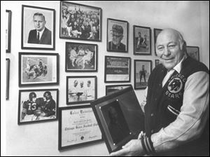 Bob Snyder displays some mementos of a lifetime in a 1986 photo. He played at Libbey High and Ohio U, then in the NFL (Cleveland, Chicago), and coached both college and NFL teams.