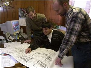 Jones & Henry workers, from left, Peter Latta, Al Zamora, and Brad Lowery look over plans.