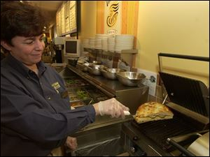 Susan Taylor of Panera Bread takes a panini from the press.