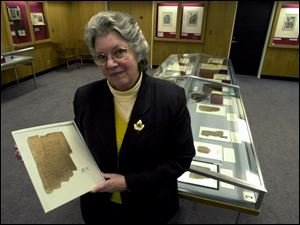 Librarian Kathryn Beam holds a papyrus codex of the Letters of St. Paul in Greek.