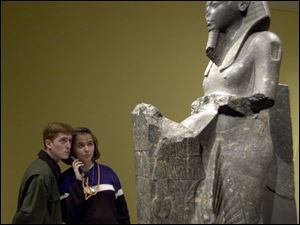 Matt Eldred, of Grand Rapids, Mich., and Andrea Chadwell, of Adrian, share an audio guide as they learn about the statute `Tutankhamun Presenting Offerings' in the exhibit at the Toledo Museum of Art.