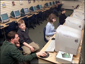 Librarian Walt Connolly helps sixth grader Tyler McMaster get on the Internet at Sylvania's Arbor Hills Junior High while seventh grader Janice Pisello and sixth graders Matt Slattery and Ben Ward work at computers, in background.