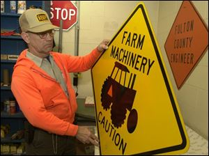 Bill Eddings, with one of Fulton County's warning signs that will keep him busy this week, will be replacing signs warning motorists of ice with ones warning of farm machinery.