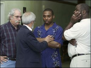 Danny Brown, right, talks with attorneys Jeff Gamso, left, and Jon Richardson outside the Lucas County common pleas courtroom where the case against him was dismissed.
