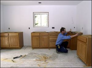 Job supervisor Jeff Mossing levels cabinets at a home in Temperance. Kitchens are among the most popular remodeling projects.