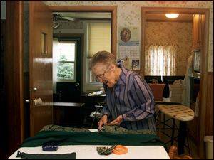 Vi Ardner sews a vestment at her Tiffin home. The General Electric retiree estimates she has stiched about 3,000 of the garments over the years.