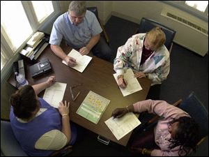 At shift change, staff members, from top, Steve Huber, Karen Adrian, Patricia Shipp, and Pam Henderson exchange notes.