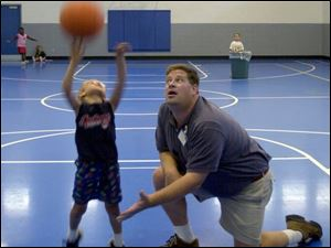Tim Yenrick, under whose direction the center has expanded greatly, shows Tyler Sarra, 7, how to shoot a basketball.