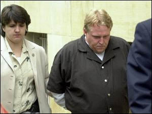 CTY August 2, 2001  Jimmie Woodland, of Fostoria,  leaves the Federal Courthouse in Toledo, Ohio under guard following his arraignment for the theft and interstate transport of the vehicle of Fred Smith of the Dayton area. Smith had been murdered previous to the theft.  [Person on left is unidentified. ] Jetta Fraser/Blade