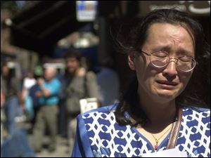 Wen Shi breaks into tears as she tries to find her husband, who worked at the World Trade Center. She was at the New York Armory, where police are establishing files on the missing.
