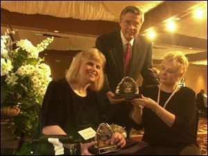 CHAMPIONS: Ann Marie Loutzenhiser, left, and Robert Savage receive awards from Liz Ference, chairwoman of the Dinner of Champions: Triumphs and Treasures. The event benefited the Multiple Sclerosis Society and was held at the Pinnacle.