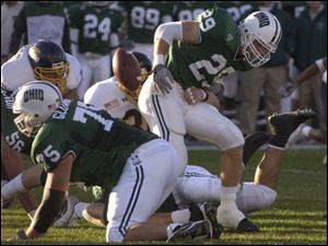 Ohio's Ray Huston has the ball knocked loose by Tom Ward, center. Ohio, which was leading the nation in rushing with 282.3 yards per game, ran for 194 yards last night.