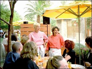 Mary Sue Milliken, left, and Toledo native Susan Feniger talk to food writers and editors on the patio of the pair's Border Grill in Las Vegas during the annual conference of the Association of Food Journalists.