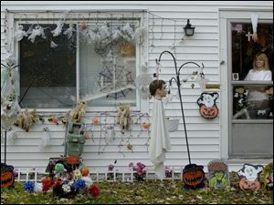 Susan Taylor admires her Halloween handiwork at her home on Oswald Street, which she decorates every holiday.