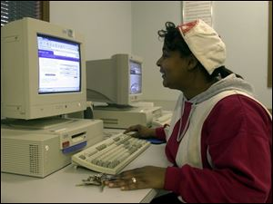 Tamara Samples does some job hunting on the computer at the Ohio Job and Family Services office on Airport Highway.
