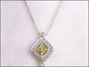 Yellow and white diamonds sparkle in yellow and white-gold settings on this delicate pendant.