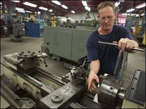 Larry Henry works on a lathe at Hause, which began in 1933 by making underground oil well equipment.