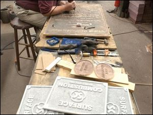 Glenn Nelson works on a bronze marker in his shop in Napoleon, where he has eight employees.