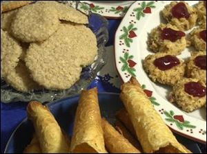 Clockwise from right, Thumbprint Cookies, Krumkake, and Danish Oat Cookies are served on Sylvia Pecsenye's Porsgrund china, top.