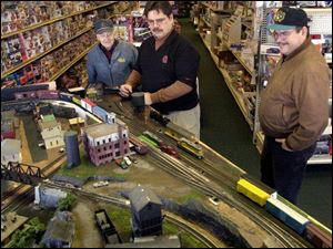 Steve Scanes, center, demonstrates a train at Steve's Hobbies in Sylvania to customers Joe Walczewski, left, and Tom Holmes. Scanes is preparing for the train show on Sunday.