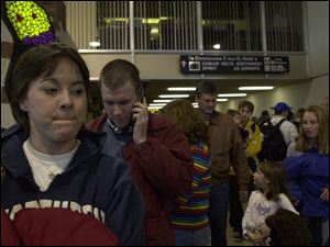 Shannon Kloss and Kyle Dinger, in foreground, wait in the security line after missing their first flight out of Detroit.