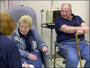 Mary and Don Griffith listen intently as nurse Cindy Peters talks about Mary's participation in this experimental drug trial.