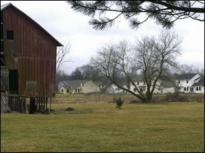 A barn at Dean and Douglas roads in Bedford Township, Michigan, contrasts with new housing developments nearby.