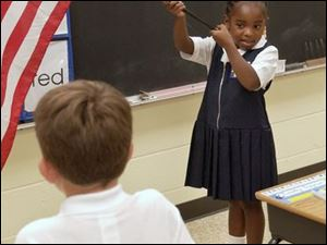 First grader Ja Shayla Motley does her part during the pledge of allegiance at Toledo's Old West End Academy.