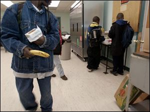 Youngsters leave with breakfast from the Kitchen for the Poor in Toledo's central city.