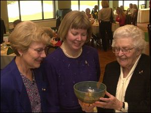 Toledo Area Delta Gamma Alumnae Group Chapter co-presidents Carol Robinson, left and Cindy Hoffman, center, look over a glass bowl with Merle Blank, who was recognized as a 65-year member of the group during the brunch at Inverness Club.