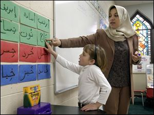 Hiam Sammara, a kindergarten teacher at the Islamic School, helps Samia Harb, 6, with her Arabic lesson.