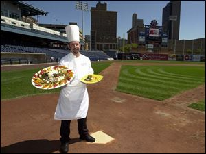 Scott Fuernstein, executive chef for Fifth Third Field, prepares everything from custom catering menus to premium ballpark food for the suites and special parties. Here he holds a feast of Grilled Chicken with Netto Pasta and Roasted Vegetables, left, and an individually plated grilled fillet entree.