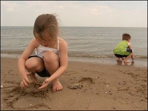 Breanna Chaffin, 4, plays in the sand while Zach Murphy, 2, hunts for stones and shells along the beach in Port Clinton.