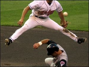 Tribe shortstop Omar Vizquel goes up and over Arizona runner Luis Gonzalez for a double play.