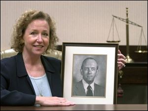 Marsha Manahan, new Toledo Bar Association president, holds a portrait of her father, Thomas Manahan, a past president of the group.
