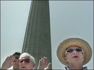 Kenneth and Myra McClure, above, who came here from Canada, take the oath of citizen- ship at Perry's Victory and International Peace Memorial.