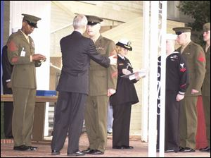 Navy Secretary Gordon England offers congratulations and a medal to Sgt. Michael Farrington of Adrian, Mich.