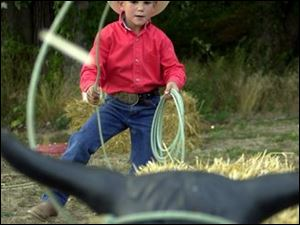 ROPE 'EM, COWBOY: Clay Vaughan, 6, lassoes his steer.