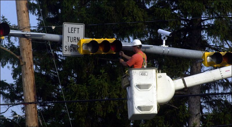 Workers install traffic signals and sensors to manage traffic at
