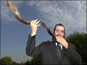 Rabbi Shmuly Rothman of Chabad House-Lubavitch demonstrates the sounding of the shofar, which signals the beginning of the High Holy Days.