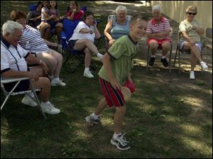 Nathan Morelock, 11, entertains relatives at the Everhardt reunion at Loop Park, Walbridge.