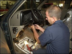 Mark Jasinski performs an ignition-switch recall repair on a Chrysler vehicle at Monroe Dodge Chrysler Jeep.
